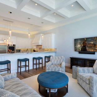 他の地域の巨大なトロピカルスタイルのおしゃれなLDK (フォーマル、無垢フローリング、暖炉なし、壁掛け型テレビ、茶色い床、グレーの壁) の写真