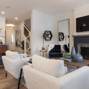 Großes, Repräsentatives, Offenes Landhaus Wohnzimmer mit beiger Wandfarbe, braunem Holzboden, Kamin, Kaminumrandung aus Holzdielen, Wand-TV und braunem Boden in Calgary