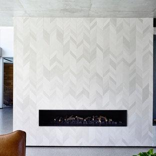 メルボルンの大きいモダンスタイルのおしゃれなLDK (グレーの壁、コンクリートの床、タイルの暖炉まわり、テレビなし、フォーマル、横長型暖炉) の写真