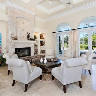 マイアミの巨大な地中海スタイルのおしゃれなリビングロフト (フォーマル、ベージュの壁、磁器タイルの床、標準型暖炉、石材の暖炉まわり、テレビなし、ベージュの床) の写真