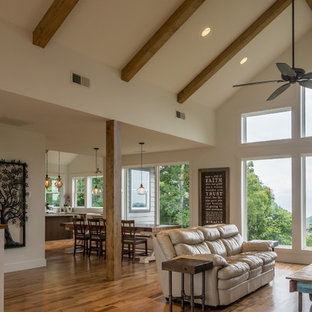 Example of a large mountain style open concept medium tone wood floor and brown floor living room design in Other with white walls and a tv stand