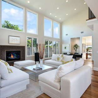 Inspiration for a transitional medium tone wood floor living room remodel in Orange County with beige walls and a standard fireplace