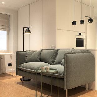 Modelo de salón para visitas abierto, casetón y papel pintado, contemporáneo, pequeño, papel pintado, sin chimenea, con paredes beige, suelo de madera clara, televisor colgado en la pared, suelo amarillo y papel pintado