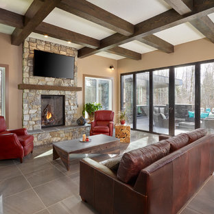 Inspiration for a large traditional formal open plan living room in Edmonton with brown walls, porcelain flooring, a standard fireplace, a stone fireplace surround and a wall mounted tv.