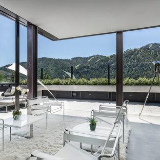 Imagen de salón abierto, actual, de tamaño medio, con suelo de cemento