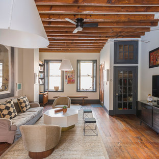 Inspiration for a large eclectic open concept dark wood floor and brown floor living room remodel in Philadelphia with white walls and a wall-mounted tv