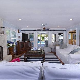 他の地域の中サイズのビーチスタイルのおしゃれな独立型リビング (フォーマル、青い壁、無垢フローリング、標準型暖炉、レンガの暖炉まわり、据え置き型テレビ、茶色い床) の写真