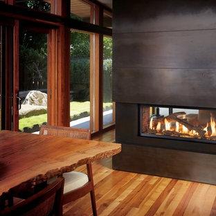 Ejemplo de salón abierto, clásico renovado, grande, con paredes marrones, suelo de madera en tonos medios, chimenea de doble cara, marco de chimenea de metal y suelo marrón