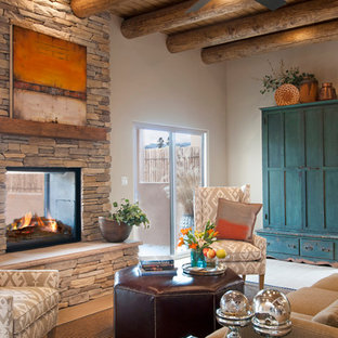 Living room - mid-sized southwestern open concept porcelain floor living room idea in Albuquerque with a two-sided fireplace, a stone fireplace and a wall-mounted tv