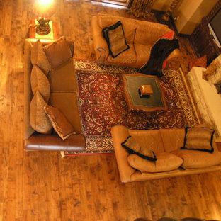 Immagine di un soggiorno stile rurale di medie dimensioni e aperto con sala formale, pareti beige, pavimento in legno massello medio, camino sospeso, cornice del camino in pietra, nessuna TV e pavimento marrone