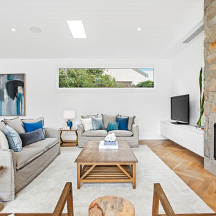 This is an example of a beach style open plan living room in Melbourne with white walls, medium hardwood flooring, a standard fireplace, a stacked stone fireplace surround, a freestanding tv, brown floors and a timber clad ceiling.