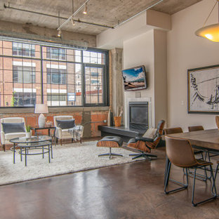 Inspiration for an industrial open concept concrete floor, brown floor and brick wall living room remodel in Minneapolis with beige walls, a standard fireplace and a wall-mounted tv