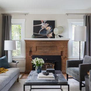 Immagine di un piccolo soggiorno chic aperto con sala formale, pareti beige, pavimento in legno massello medio, camino classico, cornice del camino in mattoni, nessuna TV e pavimento marrone
