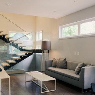 Esempio di un soggiorno minimalista di medie dimensioni e aperto con sala formale, pareti grigie, pavimento in sughero, camino bifacciale, cornice del camino in legno e TV autoportante