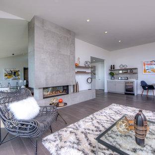 サンフランシスコの中サイズのビーチスタイルのおしゃれなLDK (フォーマル、白い壁、無垢フローリング、標準型暖炉、コンクリートの暖炉まわり、茶色い床) の写真