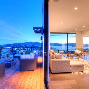 サンフランシスコの大きいビーチスタイルのおしゃれなLDK (フォーマル、白い壁、淡色無垢フローリング、標準型暖炉、コンクリートの暖炉まわり、茶色い床) の写真