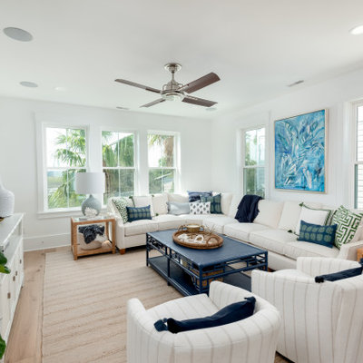 Inspiration for a mid-sized tropical open concept medium tone wood floor and brown floor living room remodel in Charleston with white walls, a wall-mounted tv and no fireplace