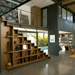 Example of a large urban open concept concrete floor and gray floor living room design in Los Angeles with black walls