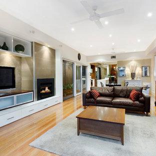 Modernes Wohnzimmer mit braunem Holzboden und freistehendem TV in Melbourne