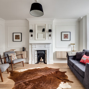 This is an example of a scandi formal living room in London with white walls, light hardwood flooring and a standard fireplace.