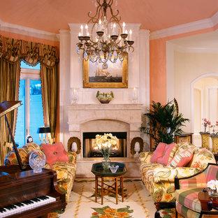 マイアミの中サイズのトロピカルスタイルのおしゃれなLDK (ミュージックルーム、ピンクの壁、無垢フローリング、標準型暖炉、石材の暖炉まわり、テレビなし) の写真