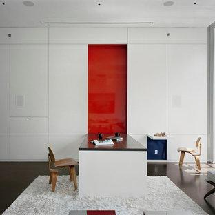 ニューヨークの広いモダンスタイルのおしゃれなリビング (赤い壁、コンクリートの床) の写真