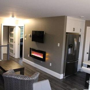 Modelo de salón abierto, contemporáneo, pequeño, con paredes grises, suelo laminado, chimeneas suspendidas, marco de chimenea de metal, televisor colgado en la pared y suelo marrón