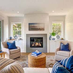 Свежая идея для дизайна: гостиная комната в морском стиле с белыми стенами, паркетным полом среднего тона, стандартным камином, коричневым полом и стенами из вагонки - отличное фото интерьера