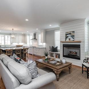 Ejemplo de salón abierto, tradicional renovado, con paredes grises, suelo de madera en tonos medios, chimenea tradicional, marco de chimenea de madera y suelo marrón