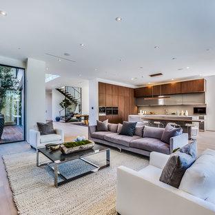 ロサンゼルスの大きいモダンスタイルのおしゃれなLDK (白い壁、淡色無垢フローリング、横長型暖炉、タイルの暖炉まわり、テレビなし) の写真
