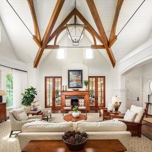 チャールストンの大きいビーチスタイルのおしゃれなLDK (白い壁、濃色無垢フローリング、標準型暖炉、木材の暖炉まわり、テレビなし、茶色い床) の写真
