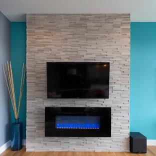 Inspiration för stora moderna allrum med öppen planlösning, med blå väggar, mellanmörkt trägolv, en bred öppen spis, en spiselkrans i sten och en väggmonterad TV