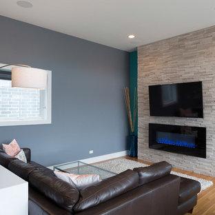 Modern inredning av ett stort allrum med öppen planlösning, med blå väggar, mellanmörkt trägolv, en bred öppen spis, en spiselkrans i sten och en väggmonterad TV