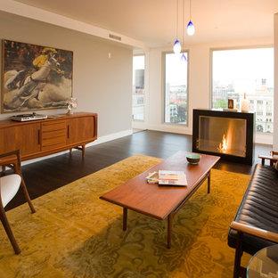 Modelo de salón para visitas abierto, vintage, grande, sin televisor, con paredes grises, suelo de madera oscura, chimenea tradicional, marco de chimenea de baldosas y/o azulejos y suelo marrón