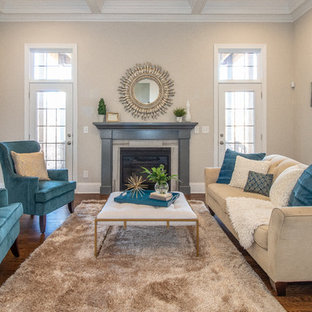 Example of a transitional enclosed medium tone wood floor and brown floor living room design in Charlotte with beige walls and a standard fireplace