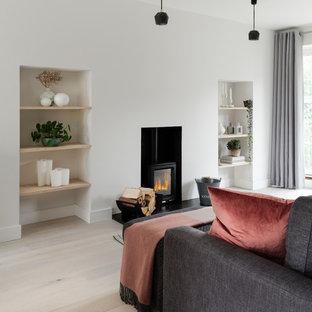 Imagen de salón abierto, actual, pequeño, con paredes blancas, suelo de madera clara, estufa de leña y suelo blanco