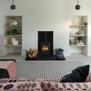 Foto de salón abierto, contemporáneo, pequeño, con paredes blancas, suelo de madera clara, estufa de leña, marco de chimenea de yeso y suelo blanco