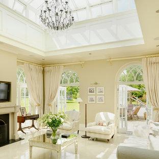 Immagine di un soggiorno tradizionale chiuso con sala formale, pareti gialle, pavimento in marmo, stufa a legna, cornice del camino in pietra e TV a parete