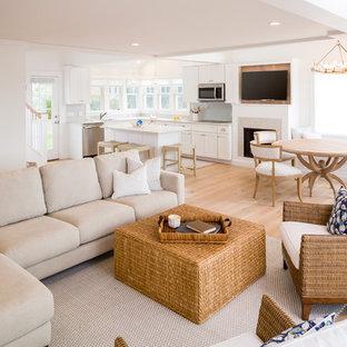 プロビデンスの中くらいのビーチスタイルのおしゃれなLDK (白い壁、淡色無垢フローリング、標準型暖炉、石材の暖炉まわり、壁掛け型テレビ) の写真