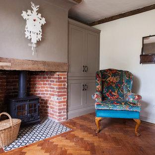 Modelo de biblioteca en casa cerrada, campestre, de tamaño medio, con paredes beige, suelo de madera oscura, estufa de leña, marco de chimenea de ladrillo y suelo multicolor