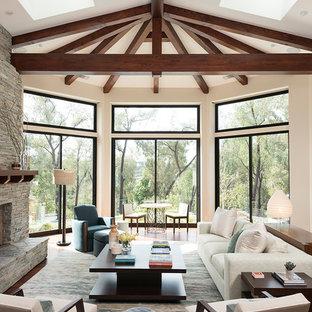 Exemple d'un salon nature fermé avec un mur beige, moquette, une cheminée standard, un manteau de cheminée en pierre et un sol multicolore.