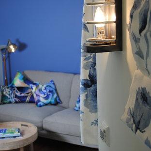 Foto de salón ecléctico, pequeño, con paredes azules, televisor colgado en la pared y suelo laminado