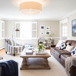 Foto de salón cerrado, tradicional renovado, grande, con paredes grises, suelo de madera clara y chimenea tradicional