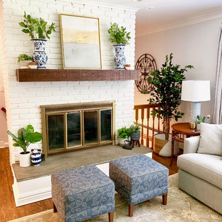Example of a mid-sized country enclosed medium tone wood floor and brown floor living room design in New York with a standard fireplace, a brick fireplace, a wall-mounted tv and blue walls