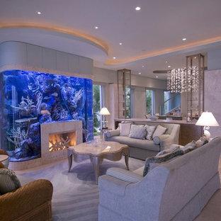 Aménagement d'un salon exotique ouvert avec un sol en calcaire, un manteau de cheminée en pierre, une salle de réception et une cheminée standard.