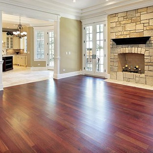 Photo of a large traditional formal enclosed living room in Denver with beige walls, dark hardwood flooring, a standard fireplace, a stone fireplace surround, no tv and red floors.