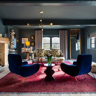 Modelo de salón para visitas abierto, moderno, de tamaño medio, con paredes azules, estufa de leña, marco de chimenea de piedra y suelo de madera clara
