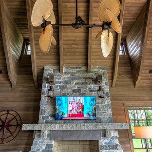 ミネアポリスの巨大なトラディショナルスタイルのおしゃれな独立型リビング (無垢フローリング、標準型暖炉、石材の暖炉まわり、ベージュの床、茶色い壁、壁掛け型テレビ) の写真