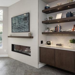 Idee per un soggiorno moderno di medie dimensioni e aperto con libreria, pareti grigie, pavimento in gres porcellanato, camino sospeso, cornice del camino piastrellata e pavimento grigio