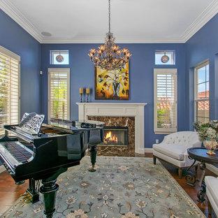 Esempio di un soggiorno chic di medie dimensioni e aperto con sala della musica, pareti blu, pavimento in legno massello medio, camino classico e cornice del camino in pietra